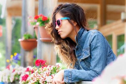 Frau im Profil zwischen Balkonblumen
